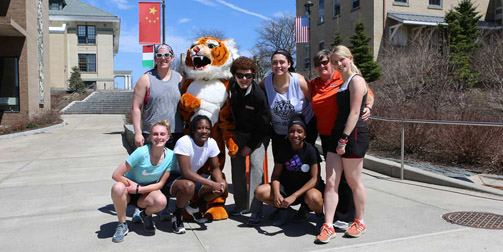 group of students pose on International Boulevard with Dr. Terenzio