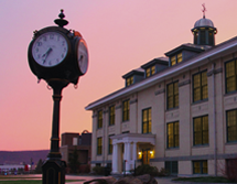 Frisbie Hall and the old clock are lit up at night with a sunset