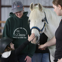 little girl petting a horse in the therepeutic program