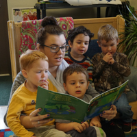 student reading to children in the classroom
