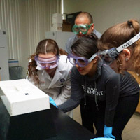 students in goggles gathered around lab equipment