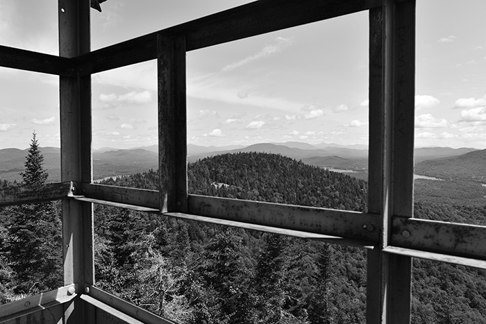 view of the adirondack mountains looking through the bars of the Owls Head Fire Tower