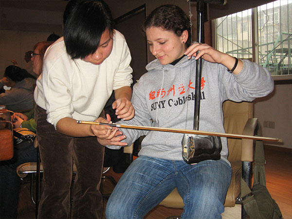 Student Caro-Anne Van Zyl learns to play a Chinese instrument.